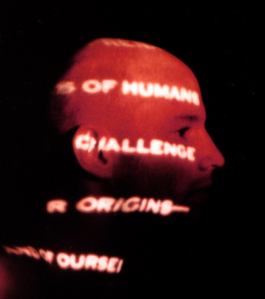 Shadowy image of a bald man's profile with words projected in white onto his head. Words say - ... S OF HUMANS ... CHALLENGE ... R ORIGINS- ... AND OF OURSE ...