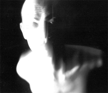 Blurry head and sholders of a bald man on a black background