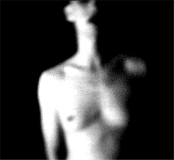 Blurry head and torso of a nude woman on a black background